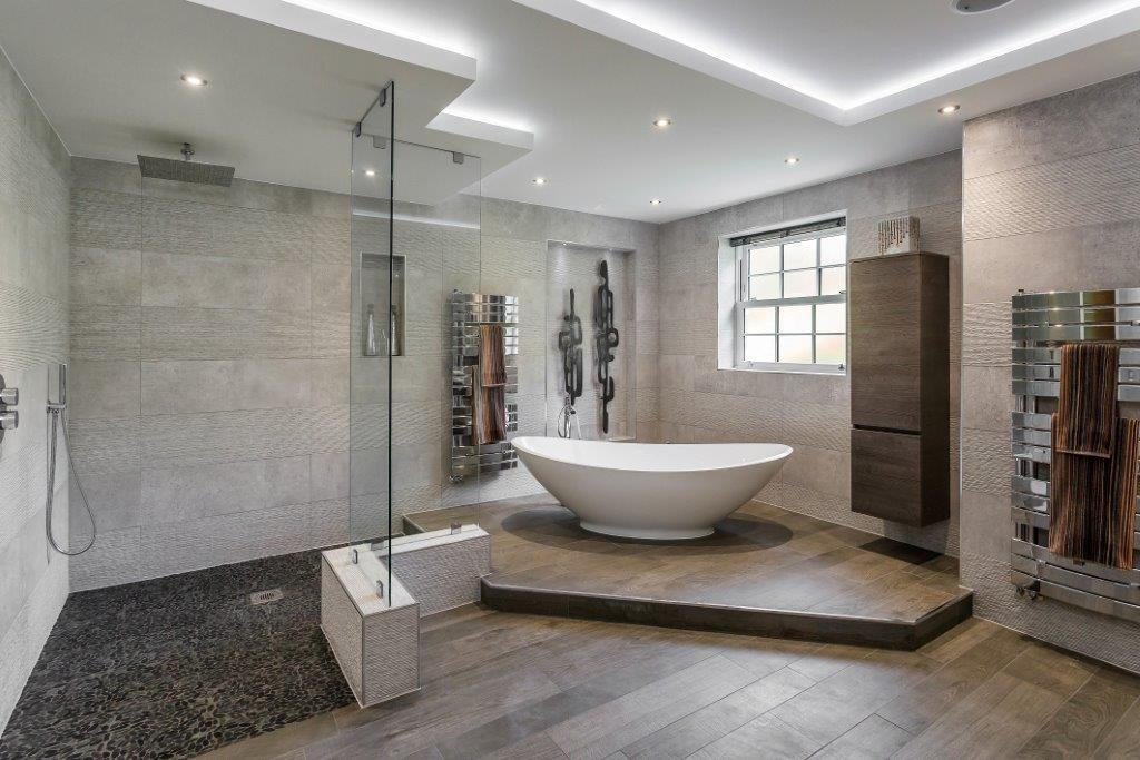Wood-look tile flooring planks, grey, installed throughout this renovated bathroom
